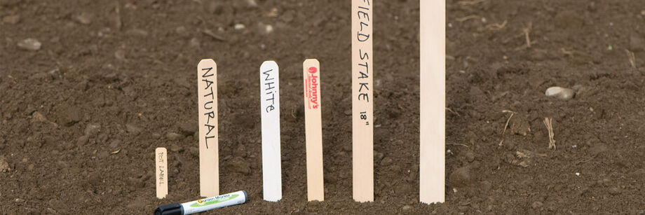 Wooden plant labels and field stakes lined up by size.