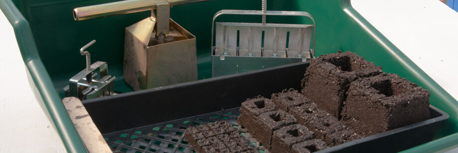 A soil blocking tray with three sizes of soil block makers and soil blocks.