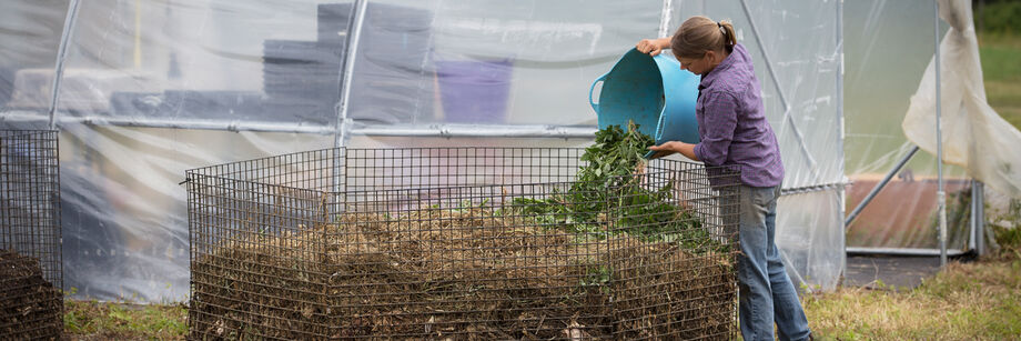Person pouring garden waste into a compost bin made of lobster trap wire.