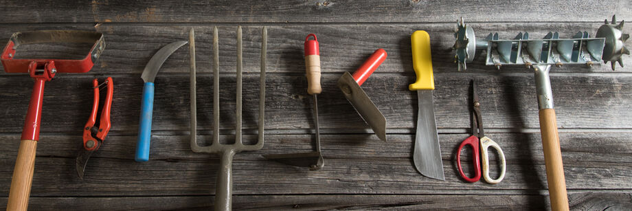 A selection of Johnny's garden hand tools laid out on a barn floor.