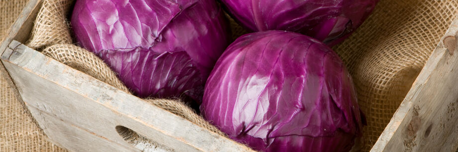 Three red cabbage heads in a wooden box.