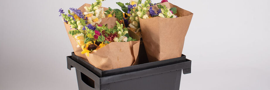 Four flower bouquets in a black plastic Procona Florida container.