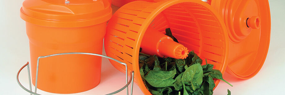 Three orange plastic commercial-grade salad spinners.