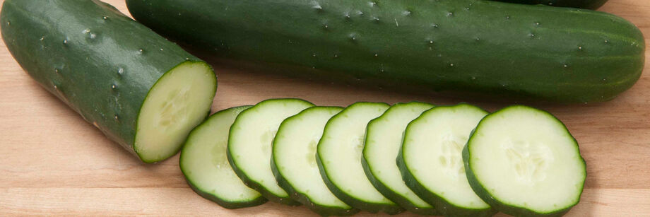 The fruit of one of our slicing cucumber varieties is laid out, whole and sliced, on a wood cutting board.
