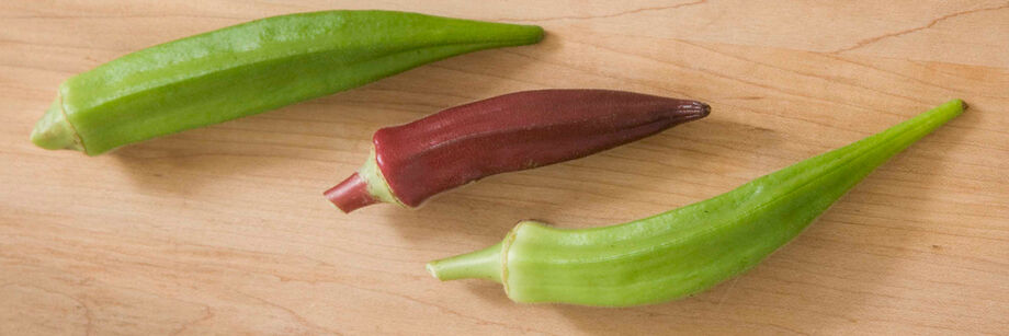 Three okra pods laid out on a wooden cutting board: two green varieties and one red variety.