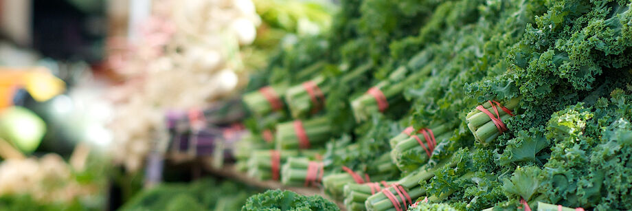 Bunches of kale for sale at a market.