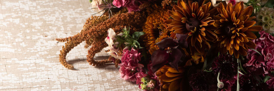 A bouquet of flowers in shades of brown, rose, and copper.