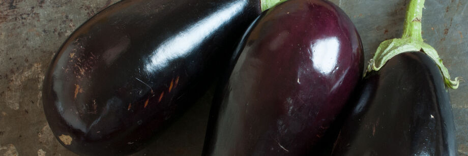 Three deep purple Italian eggplants.