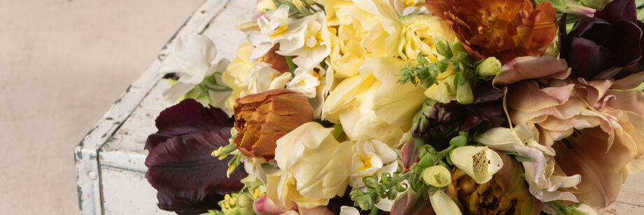 A bouquet of flowers in warm neutral colors such as cream, copper, burgundy, and pale lavender.