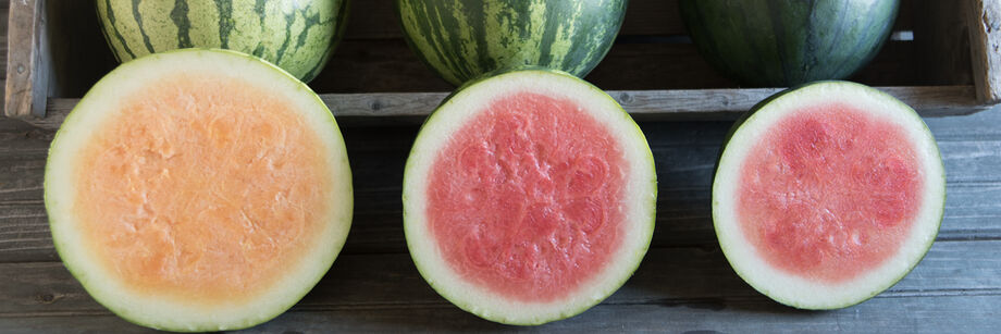 Three seedless watermelons, cut open to show pink (and in one case, orange) interiors.