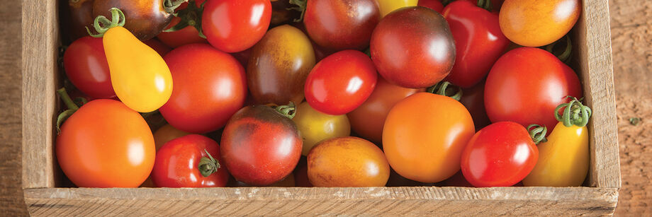 An assortment of small and colorful specialty tomatoes on display in a wooden box.