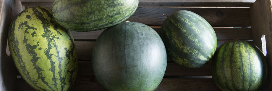 Several watermelons in a wooden crate.