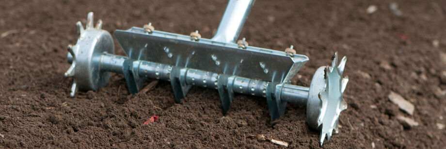 Close up of a four row seeder being used on a seed bed.