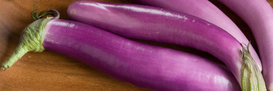 Several oblong, pale-purple Asian eggplants laid out on a table.