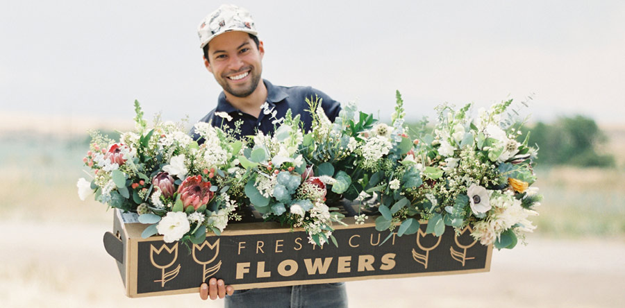 Julio Freitas, shown here with a large floral arrangement, is a contributor to our article, Pricing and Profitability for Today's Flower Farmer