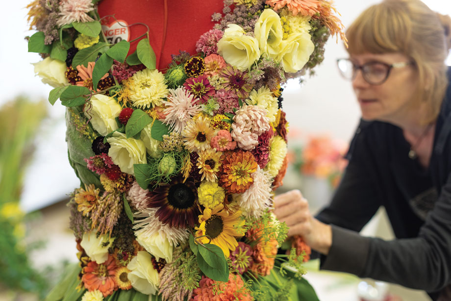 Floral Designer Rayne Grace Hoke at work on the gown
